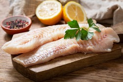 fresh fish fillet of cod with ingredients for cooking on a wooden board