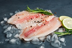 Fresh fish fillet of sea bass in ice on a dark slate background.