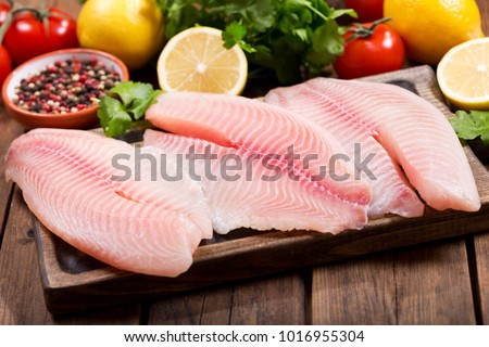 fresh fish fillet with ingredients for cooking on wooden table