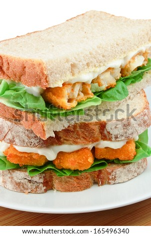Fresh Fish Finger Sandwich close up on a white serving plate