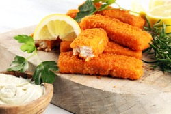 fresh fish fingers with remoulade sauce. breaded fish fingers with lemon