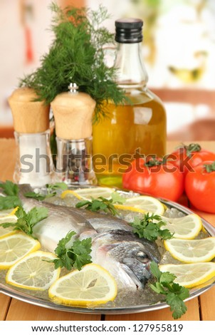 Fresh fish of dorado on tray with lemon and parsley on wooden table