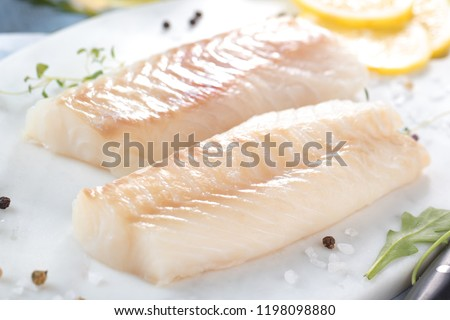 Fresh fish, raw cod fillets with addition of herbs and lemon