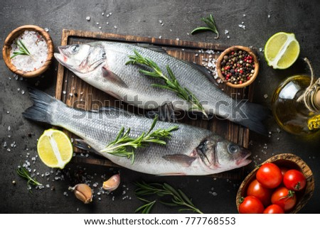 Fresh fish seabass and ingredients for cooking. Raw fish seabass with spices and herbs on black slate table. Top view.
