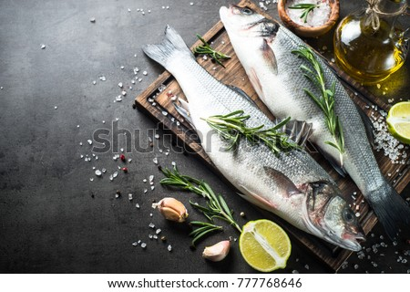 Fresh fish seabass and ingredients for cooking. Raw fish seabass with spices and herbs on black slate table. Top view with copy space.