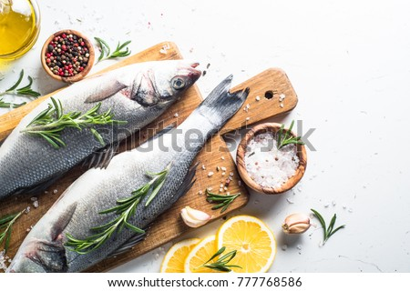 Fresh fish seabass. Raw fish seabass with spices and herbs ingredients for cooking on white background. Top view with copy space.