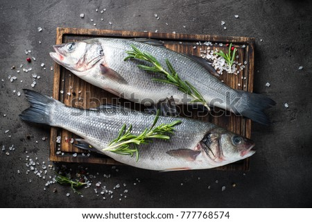 Fresh fish seabass with rosemary and sea salt on black slate table. Top view.