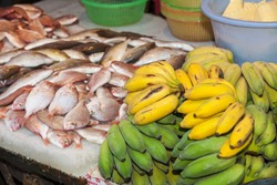 Fresh fish silver red snapper sardine and bright green bananas unripe sale during a weekend wet dry market of seafood, fruits vegetables poultry meat cooked raw fresh uncooked. Fishmarket, China.