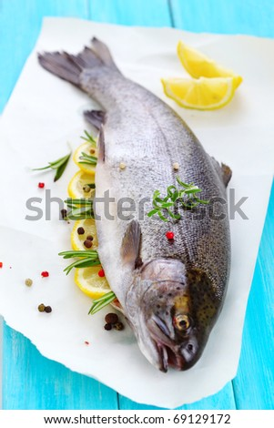 Fresh fish with lemon, rosemary and peppercorn.(Rainbow trout) - stock photo