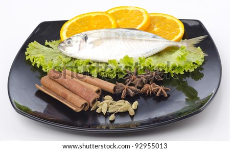 Fresh fish with lemon, salad and spices stacked on black plate isolated on white background.