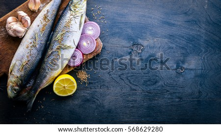 Fresh fish with lemon, vegetables, spices and oil. On a black wooden background. Free space for text . Top view