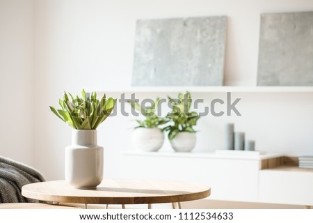 Fresh flowers in white vase placed on a small table in bright room interior with paintings, potted plants and candles on shelves in blurred background