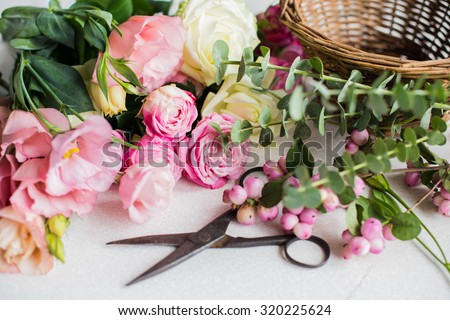Fresh flowers, leaves, and tools to create a bouquet on a table, florist\'s workplace.