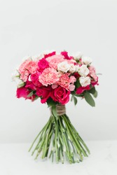 fresh flowers of roses and carnations hand bouquet standing against white background.
