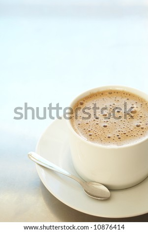 Fresh foamy cafe latte in white coffee cup on a silver background with lots of copy space Ð Shallow Depth of Field, focus on Foam