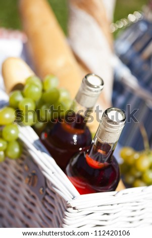 Fresh food and wine from picninc basket on grass in the garden