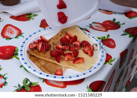 Fresh food at outdoor farmer's market. A close up view of freshly prepared pancakes on a plate, topped with fresh strawberries. Fresh food sold by a trader at a local farmers market.