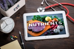 Fresh Food Ingredients & the word Nutrients on screen tablet pc, health concept. Information technology and mobile application in healthcare/medical.