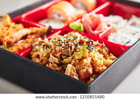 Fresh Food Portion in Japanese Bento Box with Sushi Rolls, Salad and Main Course. Rice and Fried Meat Close Up