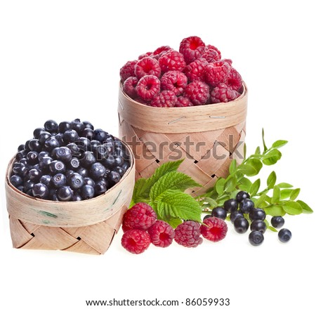 fresh forest berries : blueberries , raspberries in the basket on white