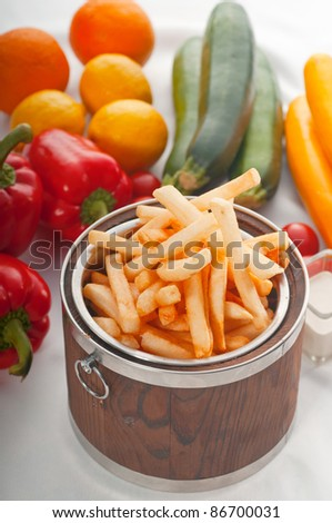 fresh french fries on a wood bucket with white dip sauce and fresh vegetables on background