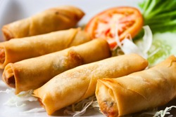 Fresh Fried Chinese Traditional Spring rolls food with green salad and tomato in dish. Traditional local food in asia.