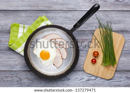 Fresh fried egg and pork ham served on pan with chives and tomatoes. English breakfast.