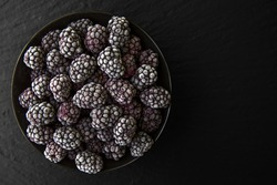 Fresh Frozen Ripe Juicy Blackberries on black background