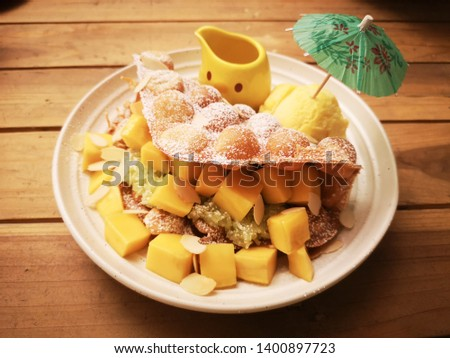 Fresh fruit and scoops of creamy special mango ice cream with Hong Kong Waffle in a scoop for serving from above.
