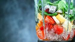 Fresh fruit and vegetables smoothie blended in blender, back view. Healthy eating concept.