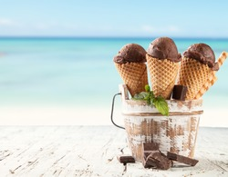 Fresh fruit ice cream scoops in cones, blur beach on background