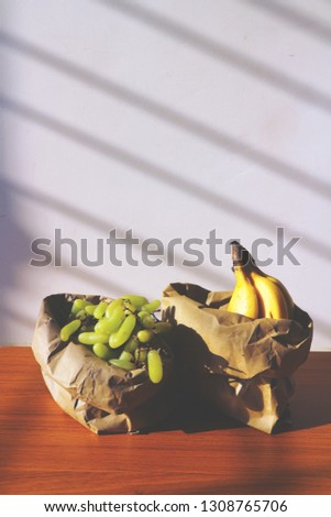 Fresh fruit in paper packaging. Life without plastic. Bananas and grapes in an environmentally friendly package.