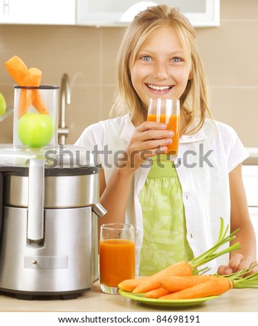 Fresh fruit juice making. Happy Girl drinking fresh carrot and apple juice in the kitchen. Juice Extractor.