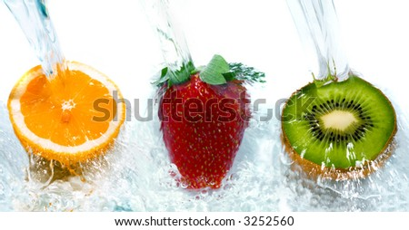 Fresh fruit jumping into water with a splash - stock photo