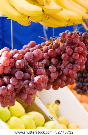 Fresh fruit on a market - grapes, banana and apples