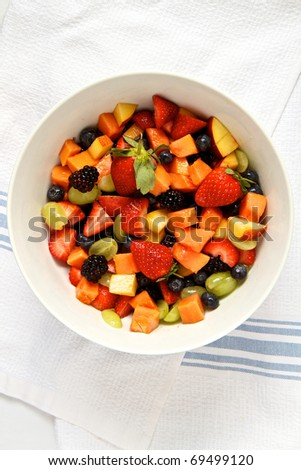 Fresh fruit salad in white bowl against cloth background