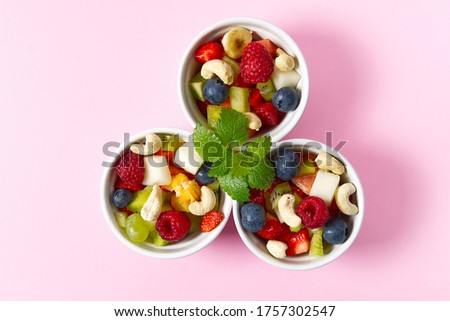 Fresh fruit salad on white bowl. Mixed fruit in white bowl healthy food style. Useful fruit salad of fresh fruits and berries on pink background. three bowls with fruit salad