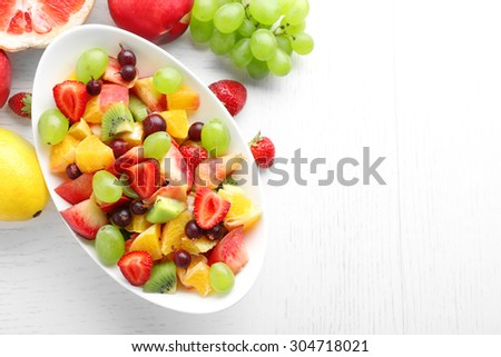Fresh fruit salad on white wooden table