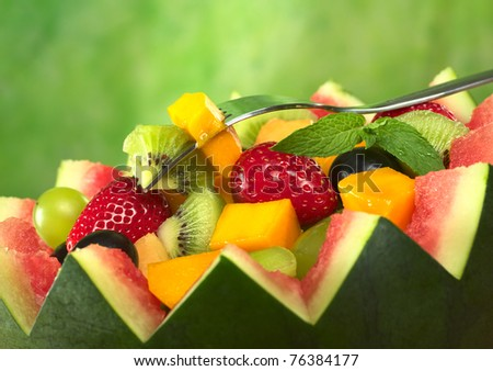 Fresh fruit salad (strawberry, kiwi, mango, grape) in melon bowl with kiwi and mango on fork and mint leaf as garnish (Selective Focus, Focus on the fruit on the fork and the mint leaf)
