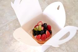 Fresh fruit tart in white paper box on table. Modern patisserie concept.