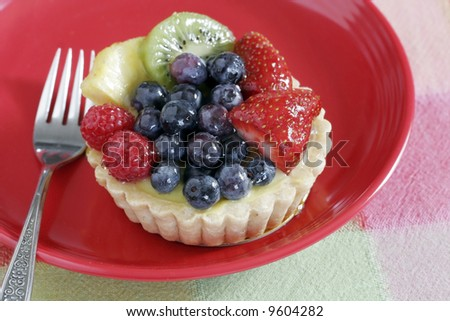 fresh fruit tart on red plate with fork
