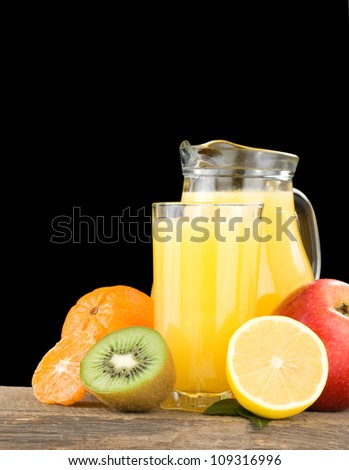 fresh fruits and juice in glass isolated on black background