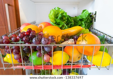 Fresh fruits and vegetables in the kitchen cabinet