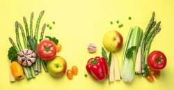 Fresh fruits and vegetables on yellow background. Healty food concept. Vegan and vegetarian diet eating. Foods high in vitamins and antioxidants. Top view