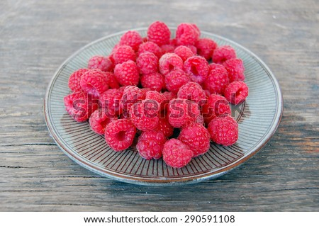 fresh fruits background with raspberries on rustic wooden table