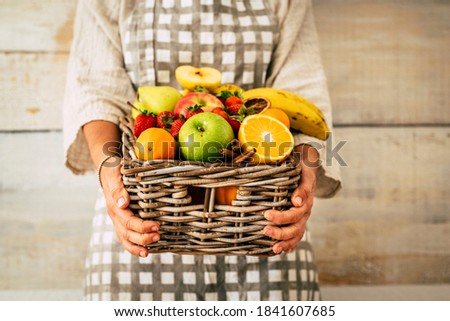 Fresh fruits bucket holded by adult woman with wall background - concept of weight loss and fruit store commerce - agriculture and farmer job lifestyle Foto stock ©
