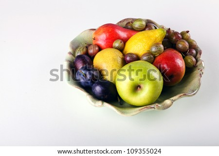 Fresh fruits  in ceramic plate on white background