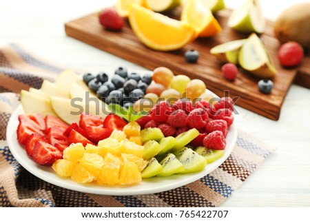Fresh fruits in plate with cutting board on wooden table
