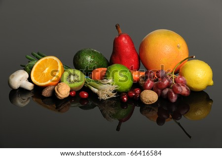 Fresh fruits, nuts, and vegetables on reflective table