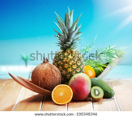 Fresh Fruits on the beach at a deck in front of an island with a palm. Assorted tropical fruits, orange,Ananas or pineapple, lime,mango and avocado.